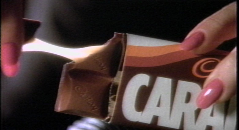A hand breaks off a piece of a Caramilk bar.