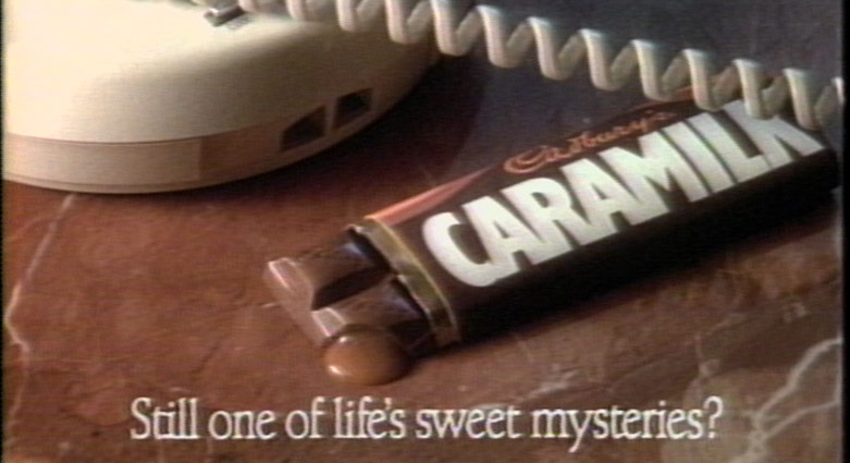 A Caramilk bar on a desk, next to a telephone.
