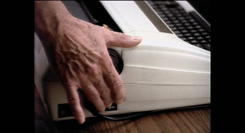 A hand turns off the power on a typewriter.