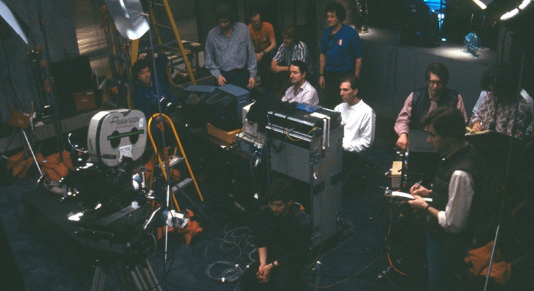 The crew of Dead Ringers working with multiple monitors.