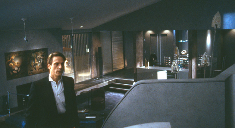 Elliot Mantle (Jeremy Irons) is seen walking in the apartment that he shares with his twin brother.