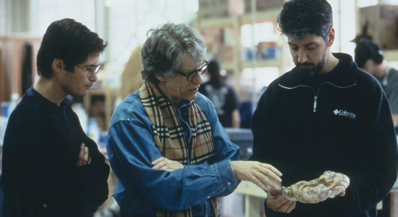 David Cronenberg discusses a disease pod prop with eXistenZ crew members.