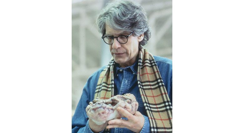 David Cronenberg holds a diseased pod in this behind-the-scenes shot.