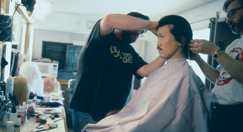 Makeup and wigs are applied on actor Oscar Hsu to hide the hydraulics system used to simulate his bloody death.