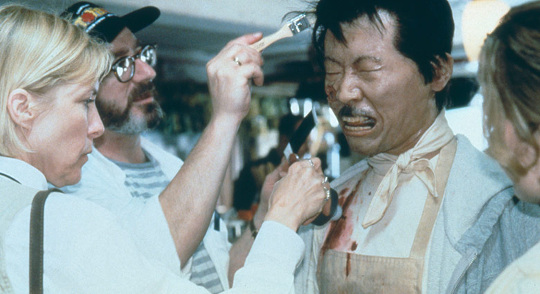 Stephan Dupuis and the special effects make-up team apply touch-ups to Oscar Hsu as the Chinese Waiter on the set of eXistenZ.