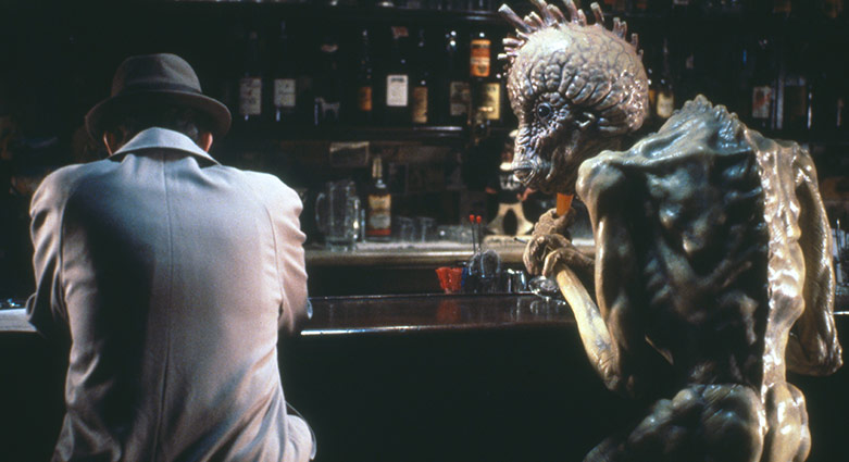 Bill Lee (Peter Weller) s'assoie au bar avec un mugwump dans Le festin nu.